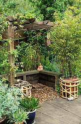 The pergola with buddha statue, windchime and Phyllostachys nigra in a container