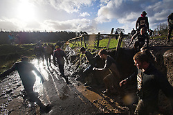 """©  London News Pictures. 27/01/2013.  Competitors run through deep thick mud as they are pushed to the limits in the 2013 Tough Guy Challenge on January 27, 2013 in Wolverhampton, England. The event has been widely described as """"the toughest race in the world"""", with over one-third of the starters failing to finish in a typical year. Photo credit: Ben Cawthra"""