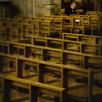 An old woman with head bowed saying prayers in an empty church