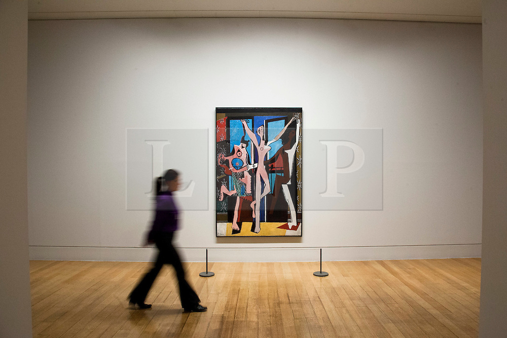 © Licensed to London News Pictures. 13/02/2012. LONDON, UK. A member of gallery staff walks past Pablo Picasso's 'The Three Dancers' at a Tate Britain exhibition exploring the artist's lifelong connections with Britain. The exhibition, called 'Picasso and Modern British Art', starts at the Tate Britain on the 15th of February 2012. Photo credit: Matt Cetti-Roberts/LNP