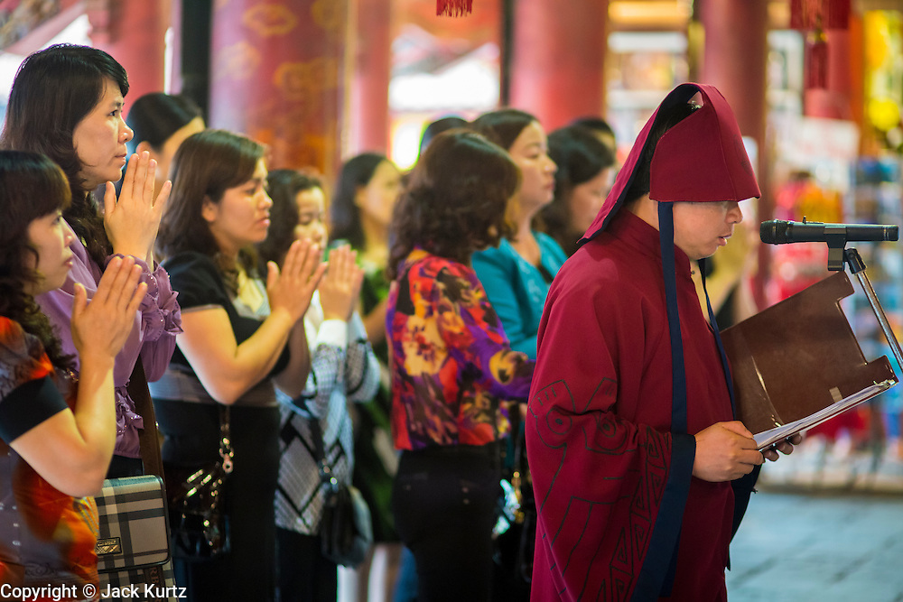 05 APRIL 2012 - HANOI, VIETNAM:   Led by a Confucian priest (right) teachers and educators pray for their students at the Temple of Literature in Hanoi, the capital of Vietnam. The Temple of Literature (Vietnamese: Vn Miu, Hán t) is a temple of Confucius in Hanoi, northern Vietnam. The compound also houses the Imperial Academy (Quc T Giám). The temple also functioned as Vietnam's first university. The temple was first constructed in 1070 under King Lý Nhân Tông and is dedicated to Confucius, sages and scholars.   PHOTO BY JACK KURTZ