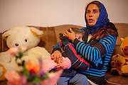 Ionela Osman with her little daughter in the living room of their house in Marginenii de Jos