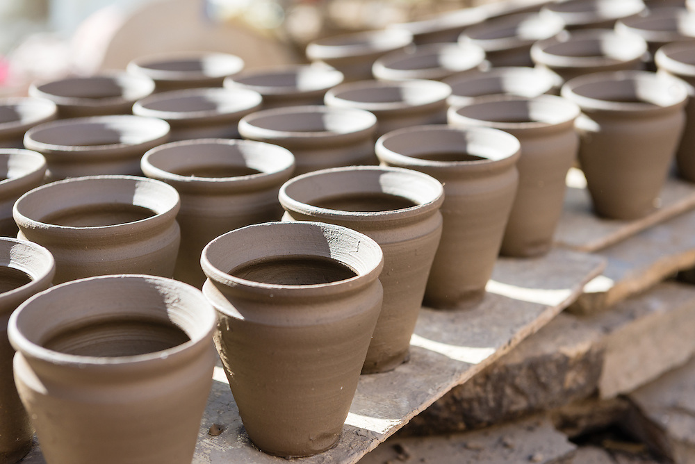 Rows of handmade clay cups drying in sun