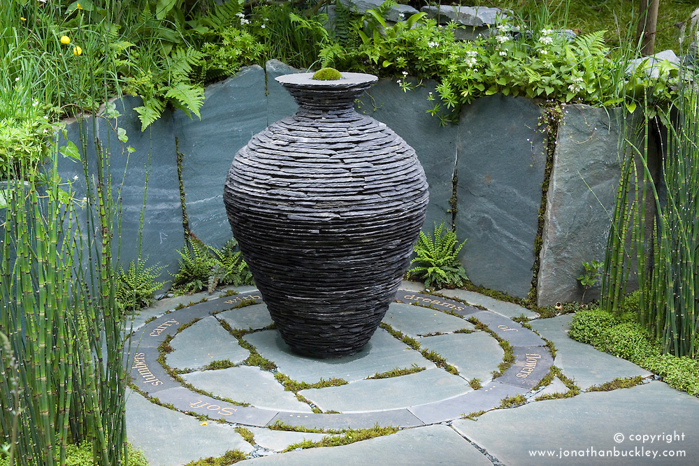 Slate urn sculpture as focal point. Slate paving engraved with words. The Cumbrian Fellside Garden.