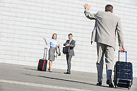 Rear view of businessman carrying luggage waving hand to colleagues