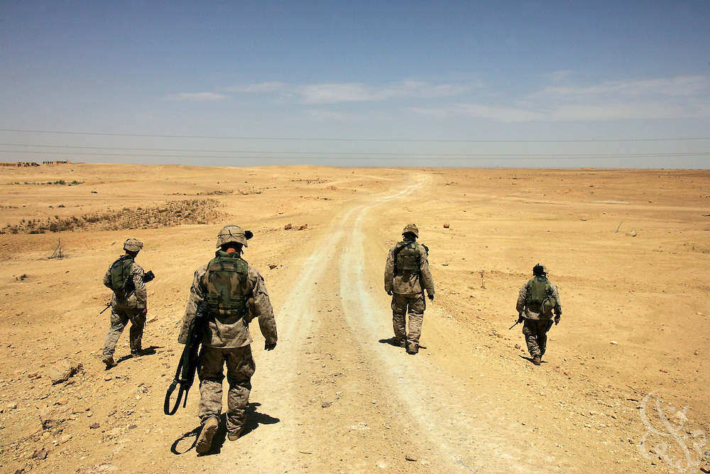 U.S. Regimental Combat Team 2 Marines search a remote desert road near the Syrian border for mines and roadside bombs during a routine mission to a radio communication tower and back May 18, 2005 near the Iraqi city of Al-Qaim.