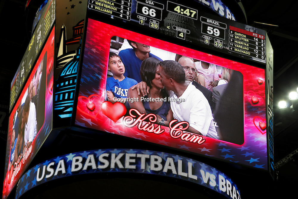"U.S. President Barack Obama and first lady Michelle Obama are shown kissing on the ""Kiss Cam"" screen during a time out in the Olympic basketball exhibition game between the U.S. and Brazil national men's teams in Washington, July 16, 2012."
