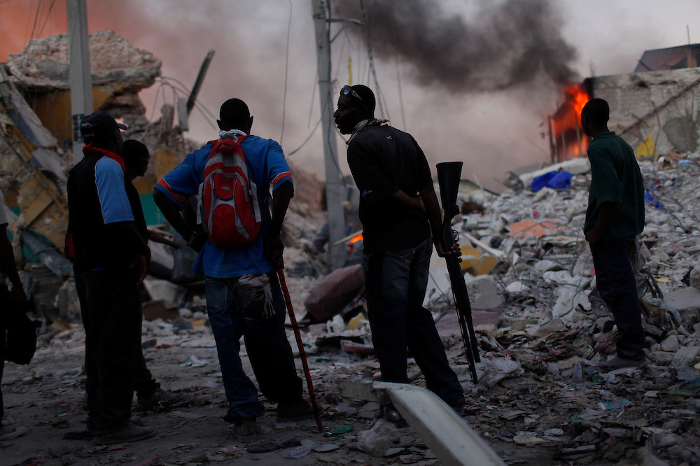 Private security forces  stand guard amid destroyed buildings  due to the Jan.12 earthquake in downtown Port-au-Prince, Haiti, Jan. 29,  2010. (AP Photo/Rodrigo Abd)