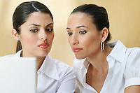 Two business women using laptop in office