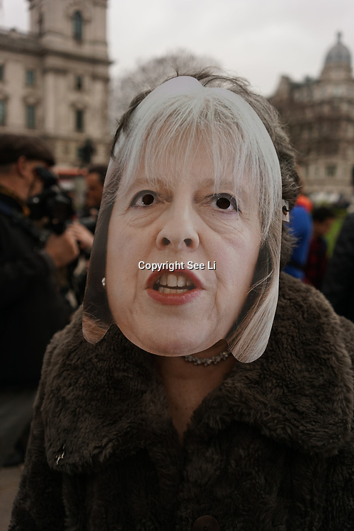 London,England,UK: 29th March 2017. A Protester wearing May mask protest against May article 50 trigger playing music in Parliament square,London,UK. by See Li