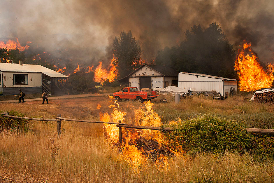Firefighters attempt to protect a home and outbuildings from the Twisp River fire near Twisp, Washington August 20, 2015.  Three firefighters in Washington state were killed and four injured while battling a wildfire threatening the town of Twisp, officials said on Wednesday, as more than a dozen major blazes burned in parched Western U.S. states. REUTERS/David Ryder