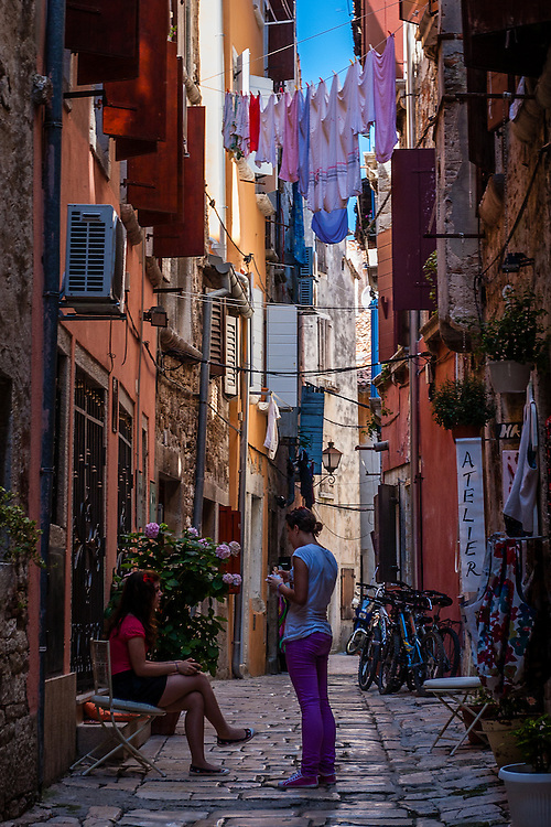 Two local girls talk on one of the many colorful back streets of Rovinj.