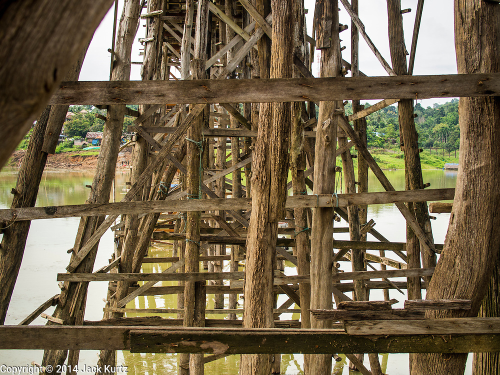 16 SEPTEMBER 2014 - SANGKHLA BURI, KANCHANABURI, THAILAND: Beneath the Mon Bridge. The 2800 foot long (850 meters) Saphan Mon (Mon Bridge) spans the Song Kalia River. It is reportedly second longest wooden bridge in the world. The bridge was severely damaged during heavy rainfall in July 2013 when its 230 foot middle section  (70 meters) collapsed during flooding. Officially known as Uttamanusorn Bridge, the bridge has been used by people in Sangkhla Buri (also known as Sangkhlaburi) for 20 years. The bridge was was conceived by Luang Pho Uttama, the late abbot of of Wat Wang Wiwekaram, and was built by hand by Mon refugees from Myanmar (then Burma). The wooden bridge is one of the leading tourist attractions in Kanchanaburi province. The loss of the bridge has hurt the economy of the Mon community opposite Sangkhla Buri. The repair has taken far longer than expected. Thai Prime Minister General Prayuth Chan-ocha ordered an engineer unit of the Royal Thai Army to help the local Mon population repair the bridge. Local people said they hope the bridge is repaired by the end November, which is when the tourist season starts.    PHOTO BY JACK KURTZ