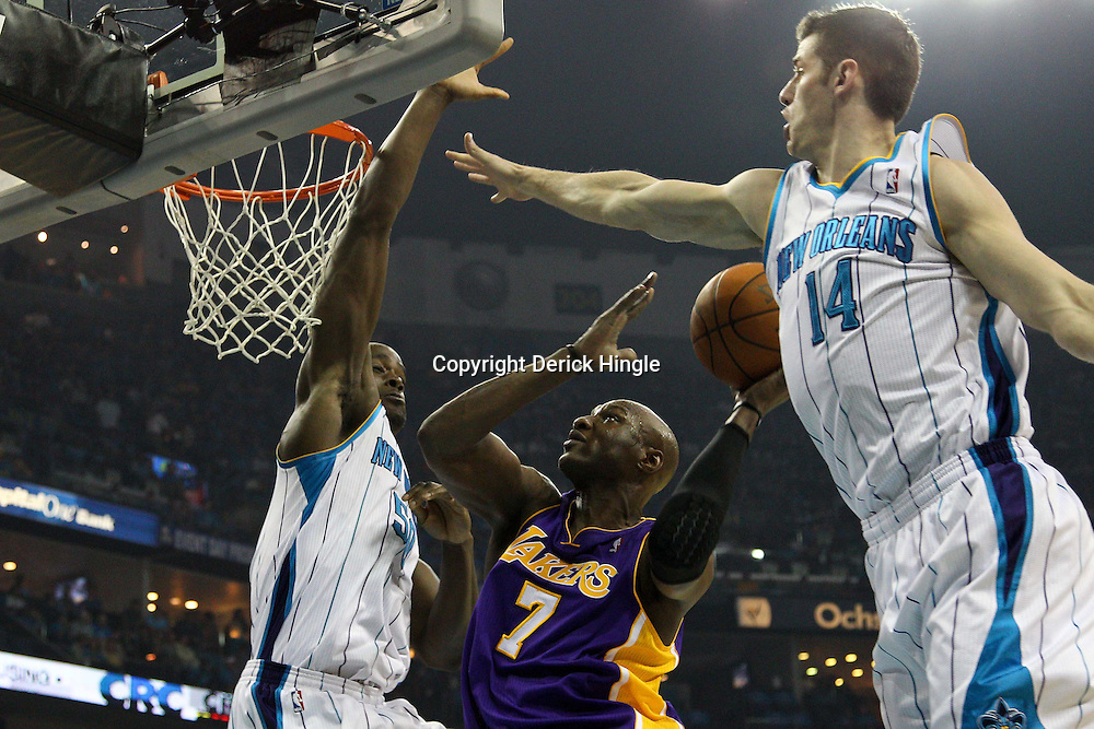 April 28, 2011; New Orleans, LA, USA; Los Angeles Lakers power forward Lamar Odom (7) shoots between New Orleans Hornets center Emeka Okafor (50) and power forward Jason Smith (14) during the second quarter in game six of the first round of the 2011 NBA playoffs at the New Orleans Arena.    Mandatory Credit: Derick E. Hingle