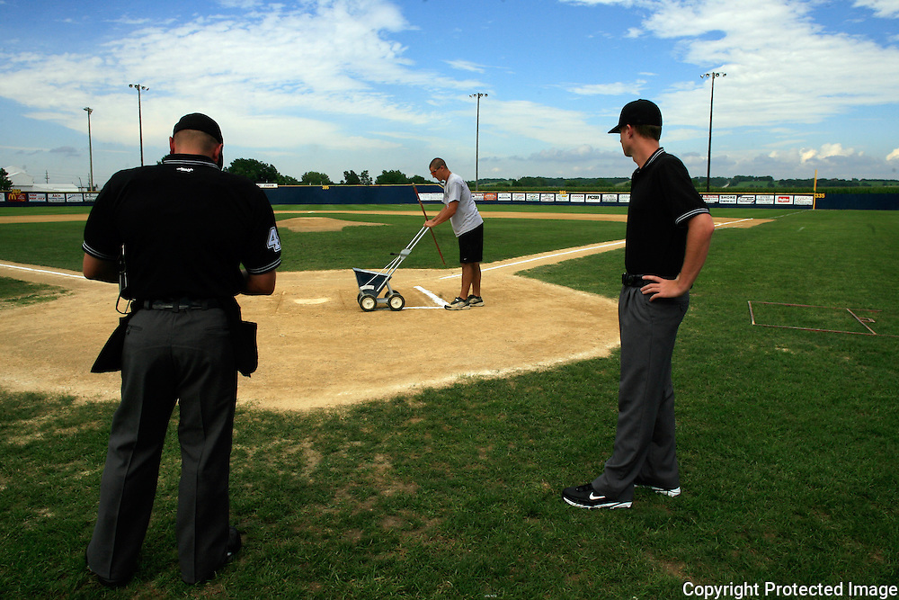 The umpires wait as the batters box is chalked before a recent Clarinda A's game at Municipal Stadium.  photo by David Peterson