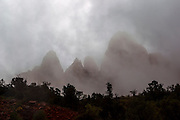 A heavy rainstorm partially obscures several peaks along Zion Canyon in Zion National Park, Utah.