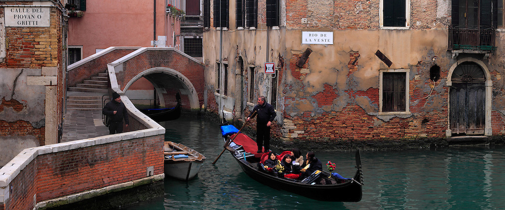 A view of Rio de la Veste, a Canal surounding the Fenice theatre in Venice, Italy, with a gondola passing by.