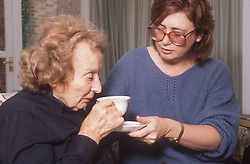 Elderly woman drinking cup of tea with assistance of daughter,