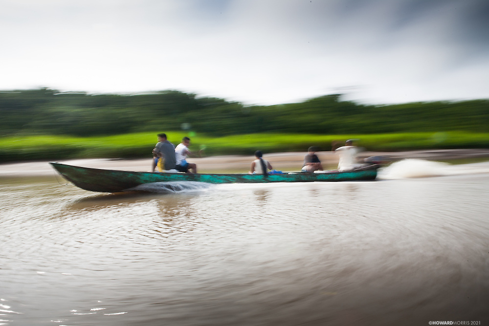 A motorized pirogue speed out to the Rio Sambu from Puerto Indio,  Darien Province, Panama.