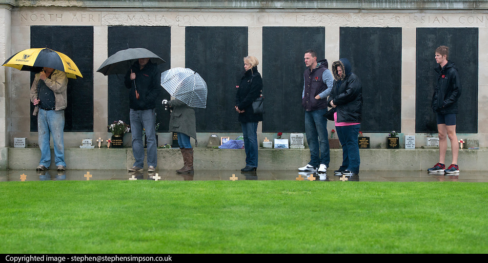 © Licensed to London News Pictures. 11/11/2014. Southsea, UK. People brace against cold and wet weather during the service. People attend a remembrance service at the Royal Naval Memorial on Southsea Common. Wet and windy weather today, 11 November 2014, at Southsea, Portsmouth. The Met Office have issued weather warnings in some parts of the UK. Photo credit : Stephen Simpson/LNP