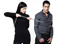 woman binding his man with a chain on white background