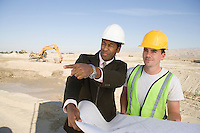 Surveyor and construction worker holding blueprint