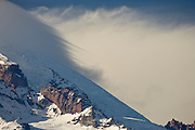 The leading edge of a lenticular cloud (Altocumulus standing lenticularis) with it's high winds leaves streaks of cloud in the air above the Ingraham Glacier and Gibralter Rock (left) on Mount Rainier. Mount Rainier National Park, WA, USA.