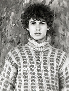 Young man wearing a turtleneck sweater leaning against tree.