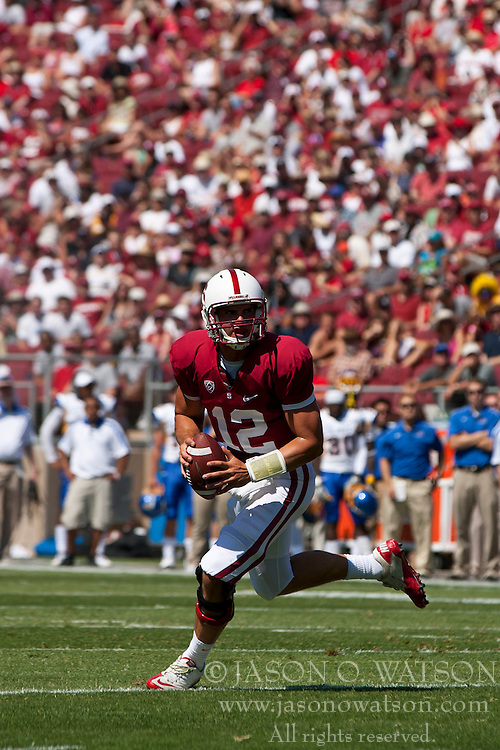 September 3, 2011; Stanford, CA, USA;  Stanford Cardinal quarterback Andrew Luck (12) rushes out of the pocket to score a touchdown against the San Jose State Spartans during the first quarter at Stanford Stadium. Stanford defeated San Jose State 57-3.