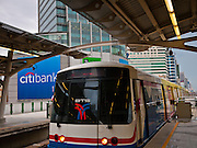 14 JULY 2011 - BANGKOK, THAILAND:   A train pulls into the Asoke station on Sukhumvit line of the BTS Skytrain in Bangkok. The Bangkok Mass Transit System, commonly known as the BTS Skytrain, is an elevated rapid transit system in Bangkok, Thailand. It is operated by Bangkok Mass Transit System Public Company Limited (BTSC) under a concession granted by the Bangkok Metropolitan Administration (BMA). The system consists of twenty-three stations along two lines: the Sukhumvit line running northwards and eastwards, terminating at Mo Chit and On Nut respectively, and the Silom line which plies Silom and Sathon Roads, the Central Business District of Bangkok, terminating at the National Stadium and Wongwian Yai. The lines interchange at Siam Station and have a combined route distance of 55 km.    PHOTO BY JACK KURTZ
