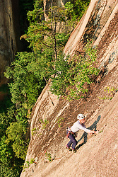 A woman rock climbing near the top of Cathedral Ledge.  Echo Lake State Park in North Conway, New Hampshire.  White Mountains.