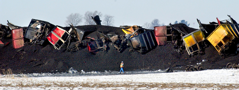 A railroad worker walks past rail cars buried by thousands of tons of coal spilled following the early morning derailment of 48 of 117 cars of a Union Pacific train, blocking  Route 90 near Edelstein, Ill..  The train, carrying coal from Wyoming to Peoria, derailed one mile west of Illinois Route 40.