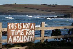 © Licensed to London News Pictures. 07/04/2020. Padstow, UK. A sign is seen in Constantine Bay village on the north coast of Cornwall shortly after the sunrise this morning. There has been backlash from local residents in Cornwall recently, advising potential visitors not to visit ahead of the Easter weekend, to reduce the spread of Coronavirus (COVID-19). Treliske Hospital in Truro is the only hospital in the county with an intensive care unit facility, with 15 beds. Photo credit : Tom Nicholson/LNP