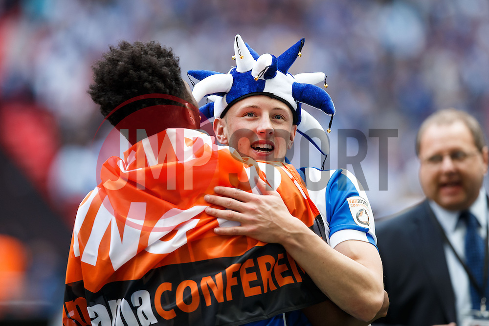 Dominic Thomas (R) hugs goalscorer Ellis Harrison after Bristol Rovers win the match on penalties  to secure promotion to the Football League 2 - Photo mandatory by-line: Rogan Thomson/JMP - 07966 386802 - 17/05/2015 - SPORT - FOOTBALL - London, England - Wembley Stadium - Bristol Rovers v Frimsby Town - Vanarama Conference Premier Play-off Final.
