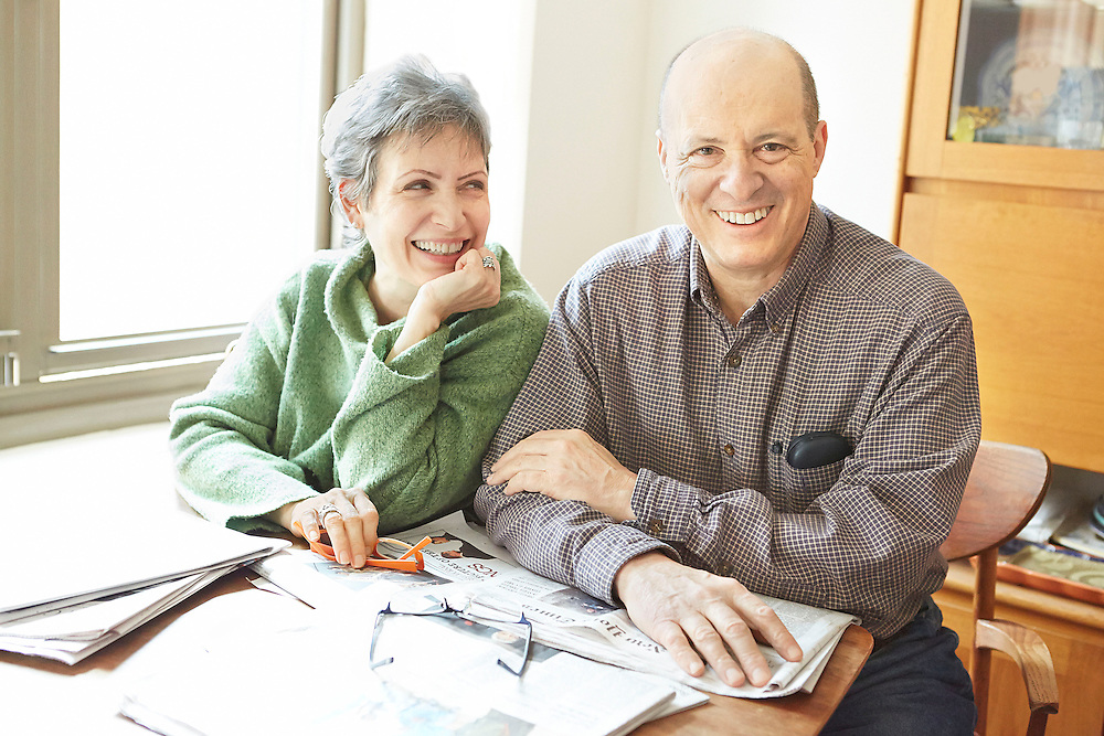 Lifestyle image of senior couple smiling while sitting at kitchen table at home