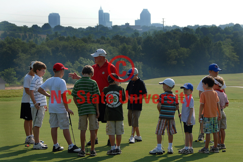 Golf campers listen to their instructor at the Lonnie Poole Golf Course. PHOTO BY ROGER WINSTEAD