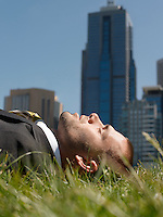 Business man lying on grass office buildings in background