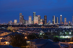 Houston, Texas skyline at dusk from west with residential neighborhood in foreground.
