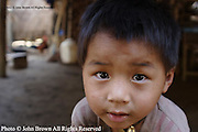 A young Karen Paduang refugee boy plays underneath his home in Ban Nai Soi, Thailand. The Karen people fled Burma (Myanmar) to escape war atrocities and are considered a tourist attraction in Thailand.
