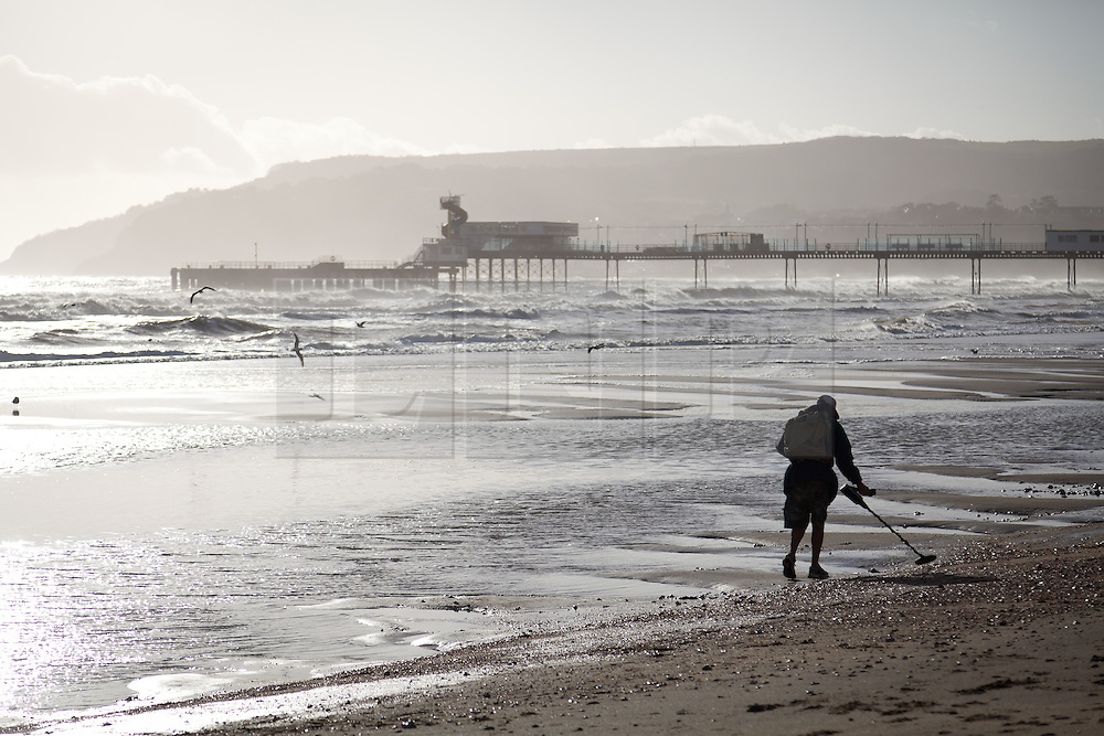 © Licensed to London News Pictures. 30/12/2013. Isle of Wight, UK.. A man uses a metal detector.  Stormy seas off of the Isle of Wight today 30 December 2013 . Photo credit : Rob Arnold/LNP