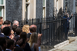 London, UK. 24 July, 2019. Theresa May, accompanied by her husband Philip and watched by her staff, waves from the steps of 10 Downing Street after addressing the nation before proceeding to Buckingham Palace to tender her resignation to the Queen.