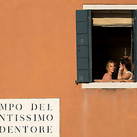 VENICE, ITALY - JULY 19:  Two girls watch from their window the procession on the votive bridge on the day of the Redentore Celebration on July 19, 2014 in Venice, Italy. Redentore , which is in remembrance of the end of the 1577 plague, is one of Venice's most loved celebrations. Highlights of the celebration include the pontoon bridge extending across the Giudecca Canal, gatherings on boats in the St. Mark's Basin and a spectacular fireworks display.  (Photo by Marco Secchi/Getty Images)