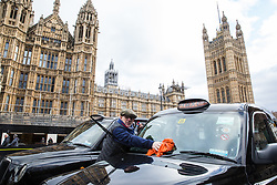 London, UK. 11th February, 2019. A licensed taxi driver cleans his vehicle during a blockade of Parliament Square and the surrounding area in protest against taxis being excluded from Bank Junction, Tottenham Court Road, Tooley Street and areas of Greenwich, Lewisham, Islington and Hackney.
