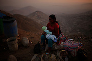 An Andean woman feeds her baby aside some plastic water containers  at the Defensores de Lima human invasion in the outskirts of the Peruvian capital, Wednesday, March 13, 2011. The 21st century Lima presents an unstoppable growing, with an evident increment on its marginal population. This uncontrolled migration from the countryside to the capital is the unwanted effect from a combination of several factors: the civil war that stroke the country's rural areas during the 80's expelling the first settlers, a decade of sustained economic growth after the violent end of the conflict,  years of political forgiveness of the Amazon and Andean areas; a cultural, political and economical centralism and the sloppy, corrupted management of public resources.  Despite its enormous water vulnerability and limitations - having been built over the sand dunes reaching the Pacific Ocean, being influenced by a rainless weather pattern and relying in the water supply from melting Andean glaciers - Lima still lures and moves thousands of farmers and people from the countryside in search of better education and jobs at the desert city. The survival challenges for this huge human settlement of 8 million souls are defined by its water resources. Its growing and living standard defined by the absence of it. The colonization of the area , a historic mistake never committed by the Inca empire, but which the Spaniards prefer to ignore in their search for wealth is the curse of a growing population and retreating water supply.   (Photo Dado Galdieri)