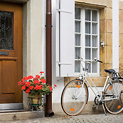 White bicycle parked outside door of home, Murten, Switzerland<br />