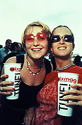 Two smiling women wearing sunglasses, grasping paper cups, Ibiza, 1990s.