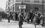 A Jewish policeman and a German soldier direct pedestrian traffic across the main street dividing the two parts of the Lodz ghetto, Poland. Second World War.