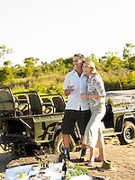 Couple on picnic during safari smiling jeep in background