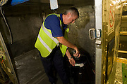 A British Airways baggage handler scans the bar code of his airline passenger's item of luggage before loading in container