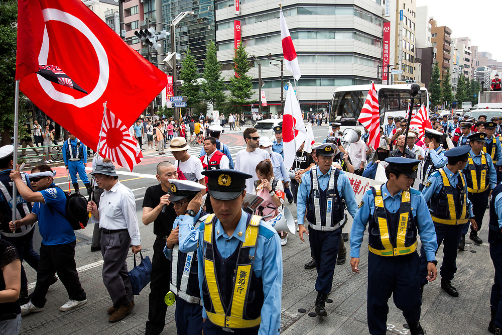 "TOKYO, JAPAN - JULY 16: Japanese nationalists holding Japanese flags took to the streets in a ""hate demonstration"" in Akihabara, Tokyo, Japan on July 16, 2017. The nationalists faced off with anti-racist groups who mounted counter protests demanding an end to hate speech and racism in Japan. (Photo by Richard Atrero de Guzman/NUR Photo)"